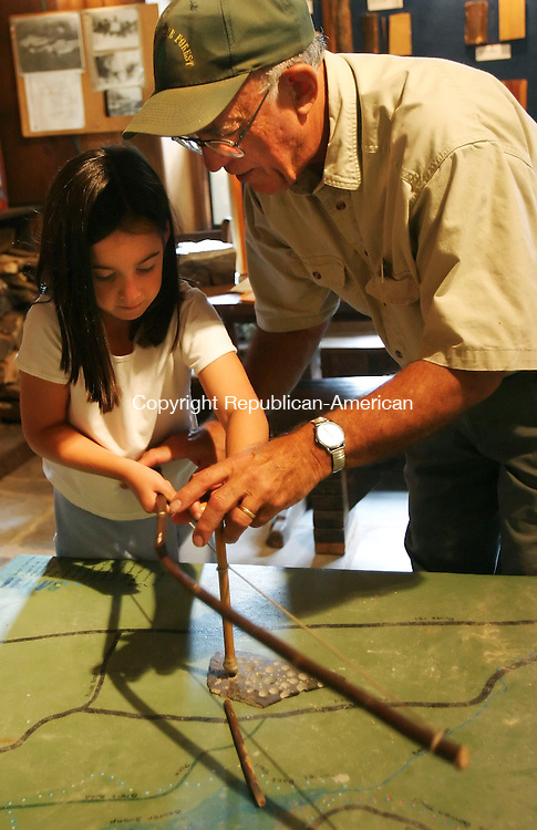 BARKHAMSTED,  CT 18 September 2005 -091805BZ18- Hallie Mather, 8, of Canton, gets help from Walt Landgraf, naturalist and curator,  while learning how to use a bow drill at the Stone Museum in the People's State Forest.  Mather was drilling holes into slate with a flint-tipped stick.<br /> Jamison C. Bazinet / Republican-American