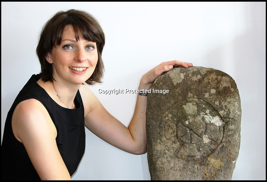 BNPS.co.uk (01202 558833)<br /> Pic: Dukes/BNPS<br /> <br /> Valuer Amy Brennan with the 1100 year old headstone.<br /> <br /> An extremely rare Anglo-Saxon gravestone dating from the time of Alfred the Great has been discovered propped against a garage wall in Surrey.<br /> <br /> The 3ft tall slab once stood on the grave of a 9th century christian Anglo-saxon - despite originally being found in Little Eaton in Derbyshire, an area that would have been ruled by the pagan Viking invaders at the time under 'Danelaw'<br /> <br /> The incredibly rare 1100 year old stone is carved with Christian symbols and was found by a sharp eyed auctioneer Guy Swinge hiding among cardboard boxes and garden tools in a garage at a house in Surrey.<br /> <br /> Dukes auctioneers are now selling the historic object with a £5000 estimate.