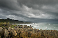 Punakaiki coastline under rain and stormy clouds with pancake rocks in foreground, Paparoa National Park, Buller Region, West Coast, South Island, New Zealand, NZ