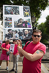 """© Joel Goodman - 07973 332324 . 10/08/2013 . London , UK . A protester with a placard with images of violence against gay people overlaid with the logos of Sochi Olympic Games sponsors , which are due to be held in Russia in 2014 . Demonstration against homophobic laws being enacted in Russia on Whitehall this afternoon (10th August 2013) . Legislation includes banning gay pride events for100 years , banning the distribution of """" propaganda of non-traditional sexual relations """" to minors , making it illegal for the adoption of Russian children by gay couples or any single person who comes from a country that recognises marriage equality and giving authorities the rights to arrest foreign nationals whom they suspect are LGBT or pro gay with the right to detain them for up to 14 days. Photo credit : Joel Goodman"""