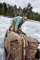 Canoeists drag and push their canoe over a frozen lake during an early spring trip to Lady Evelyn-Smoothwater Provincial Park in Ontario Canada.