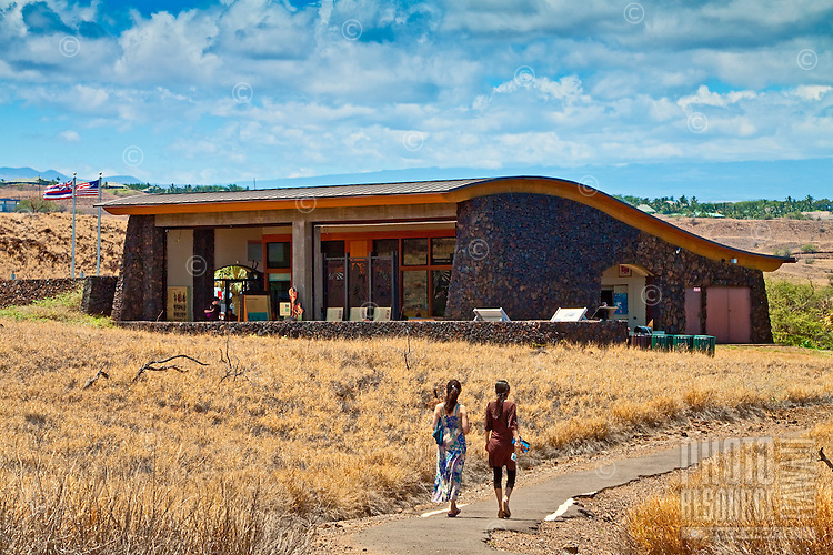 Two visitors walking toward the visitor center at Pu'ukohola Heiau National Historic Site, Kawaihae, Kohala, Big Island.