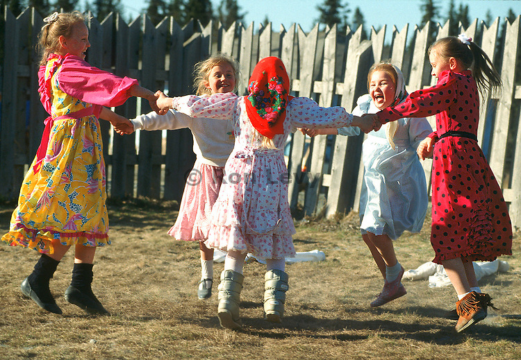 Traditional Russian girls swing around in merry-go-round in Nikolavesk, one of the few Russian villages left in Alaska, on the Kenai Peninsula near Homer.