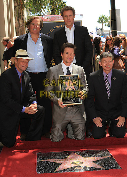 LORENZO DI BONAVENTURA, MARK WAHLBERG & WILL FERRELL.Mark Wahlberg is honored on The Hollywood Walk of Fame with the 2414th Star, Hollywood, CA, USA, .29th July 2010..full half  length grey gray suit tie shirt holding frame kneeling  .CAP/ADM/FS.©Faye Sadou/AdMedia/Capital Pictures.