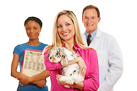 Series with a Cacucasian Veterinarian, and mixed-ethnicity group of assistants and customers.  Holding rabbit, cat and dog.  Isolated on white.
