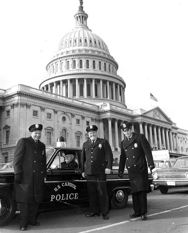 This photo was taken in January or February 1965.  The construction in the background is the Inaugural stands built for President Lyndon Johnson's swearing-in in 1965.  Policeman on the left is Officer Ralph Scalzo.  The officer seated in the squad car is Albert Samuels. Officer Samuels joined the Capitol Police in 1948 shortly after being honorably discharged from the U.S. Army. He served as a Capitol police officer for more than 35 years, and retired in 1984 with the rank of Lieutenant. (We have no idea why the flag is at half-mast.) LtoR Ralph Scalzo, Albert Samuels and Paul Singleton. Policeman on right is unidentified.