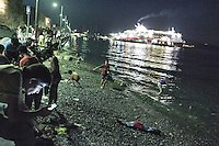 Beach at night with refugees from Pakistan. their children play at the breakwaters. Behind them the ferry that they hope to take to Athens. Kos, Greece. Sept. 6, 2015