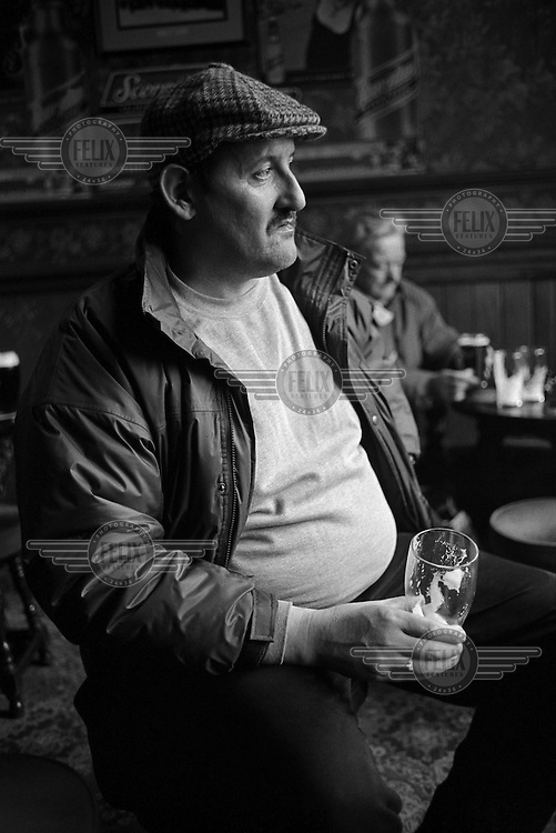 An unemployed ex-miner drinks a pint of beer in a pub in Rotherham.