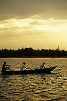 Silhouette of three boys paddling boat across Thu Bon River, Hoi An, Vietnam