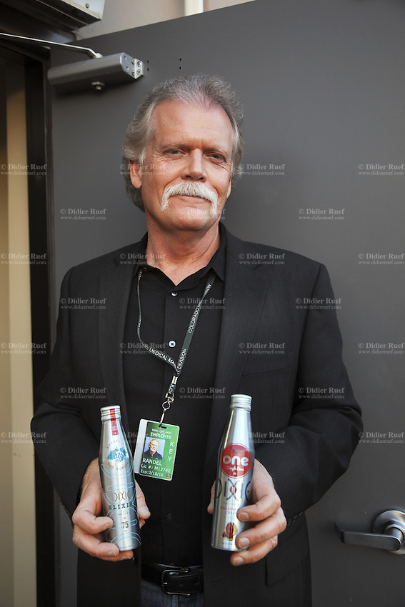 USA. Colorado state. Denver.  Randy Hadden-Good is the general manager of Dixie. Established in 2010 as allowed by Colorado House Bill 1284 (cannabis liberalization), Dixie Elixirs and Edibles manufactures seven premium THC-infused product lines. As the leader in medical marijuana infused products, Dixie was proud to receive the first Infused Products Retail Marijuana License. The man is holding in his hands two bottles of Dixie Elixirs™ (THC-infused cannabis soda) which are handcrafted and formulated for optimal cannabinoid delivery. Carbonation supports rapid THC delivery and refreshing flavors ensure all customers to sit back with friends and enjoy. The marijuana drinks are available in 5mg, 40mg and 75mg and come in a variety of expertly developed flavors. Cannabis, commonly known as marijuana, is a preparation of the Cannabis plant intended for use as a psychoactive drug and as medicine. Pharmacologically, the principal psychoactive constituent of cannabis is tetrahydrocannabinol (THC); it is one of 483 known compounds in the plant, including at least 84 other cannabinoids, such as cannabidiol (CBD), cannabinol (CBN), tetrahydrocannabivarin (THCV), and cannabigerol (CBG). 18.12.2014 © 2014 Didier Ruef