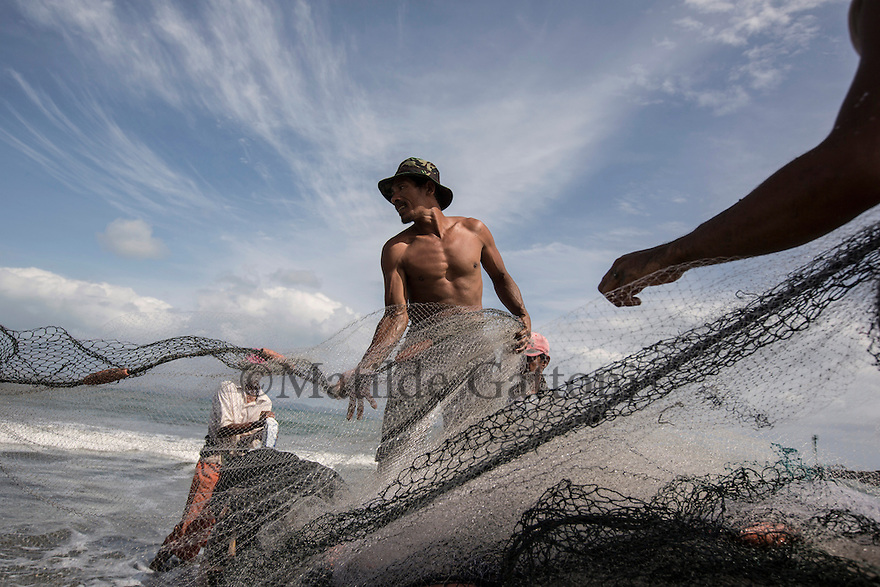 Indonesia – Sumatra - Banda Aceh – Gampong Kawa Beach- Ismail Ibrahim, a 52- year-old fisherman is gathering the nets on his boat preparing to leave for the ocean. On the morning of the 26th of December of 2004, Ismail was sleeping in his house in Merduati when the tsunami stroke. In the chaos, his wife and four kids lost track of each other and reunited only after two weeks. After spending almost two years at a relocation center since their house was destroyed, Ismail's family was relocated in Panteriek, an area far from the sea. Ismail decided to sell the house and buy a plot of land in a slum in Gampong Jawa. Whenever he is bored or sad he just sits on the beach and the sea takes away the sorrow. His relationship with the ocean hasn't changed after the tsunami contrary to his wife who is still traumatized by the event.