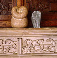 An abstract sculpture and a minimalist elephant in grey stone are displayed on the intricately carved mantelpiece in the dining room