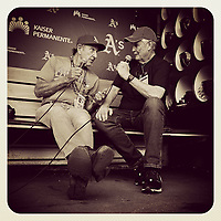 OAKLAND, CA - JULY 26: iPhone Instagram of photographers Michael Zagaris and Peter Read Miller producing a video while sitting in the A's dugout before a game at the Oakland Coliseum on July 26, 2019 in Oakland, California. (Photo by Brad Mangin)