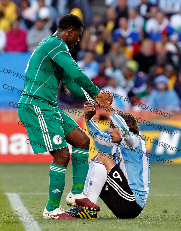 Yakubu Ayegbeni of Nigeria helps Gabriel Heinze of Argentina to get up during their group B match at a Ellis Park Stadium in Johannesburg, South Africa, Saturday, June 12, 2010. 12.6.2010 (credit & photo: Pedja Milosavljevic / +381 64 1260 959 / thepedja@gmail.com / STARSPORT )