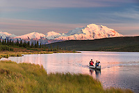 Man and women in a canoe in Wonder Lake as alpenglow light falls on Mt. Denali, Denali National Park, Interior, Alaska
