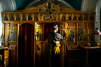 Mount Athos - The Holy Mountain.<br /> Father Iusif lights candles inside his church that he built. <br /> <br /> Photographer: Rick Findler