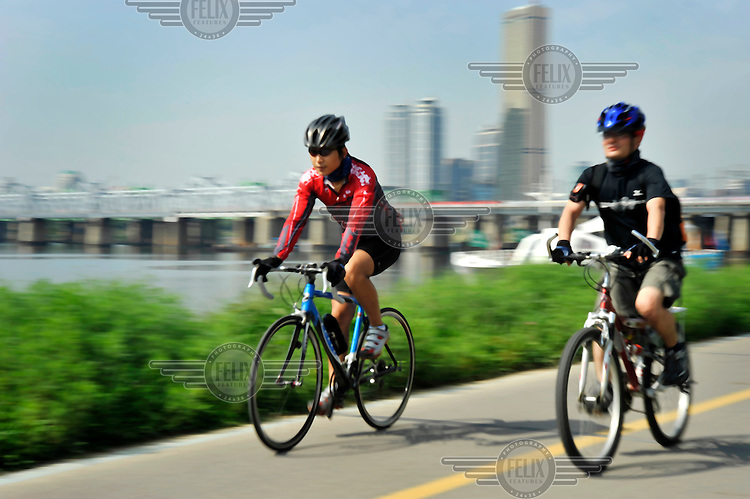 Cyclists ride alongside the Han River, the main river flowing through Seoul.