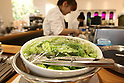 July 12, 2010 - Tokyo, Japan - A chef prepares a salad which are being grown under fluorescent light at the 'Urban Farm Pasona Group Headquaters' in Tokyo, Japan, on July 12, 2010. Aiming for an amicable working environment with 'Symbiosus with Nature' as a concept, more than 200 types of fruits and vegetables grow in the nine-floor building's verandas.