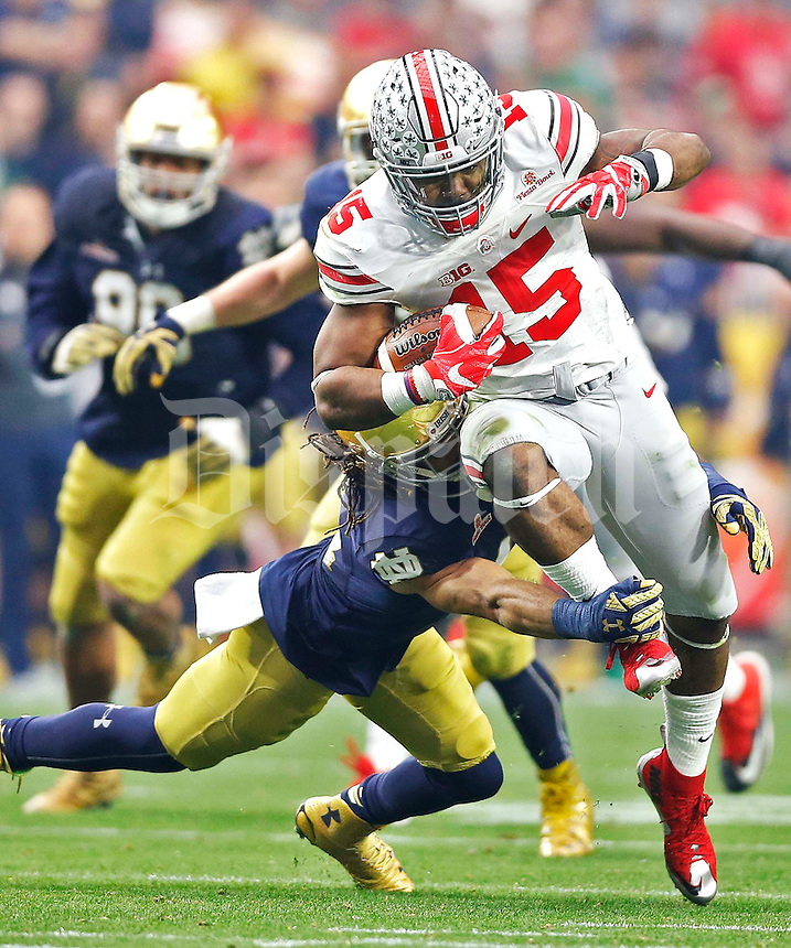 Ohio State Buckeyes running back Ezekiel Elliott (15) drags Notre Dame defenders towards the end zone in a second quarter run at University of Phoenix Stadium in Glendale, AZ on January 1, 2016.  (Chris Russell/Dispatch Photo)