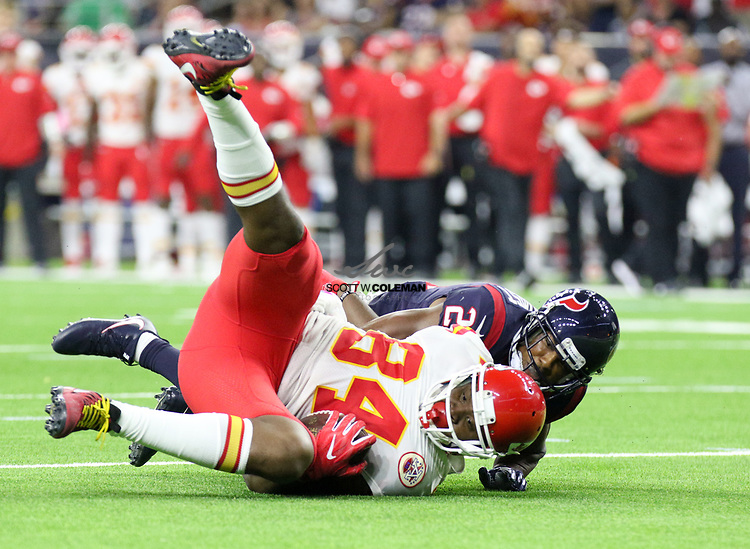 Houston Texans strong safety Marcus Gilchrist (21) tackles Kansas City Chiefs tight end Demetrius Harris (84) during the second quarter of an NFL game between the Houston Texans and the Kansas City Chiefs at NRG Stadium in Houston, Texas.