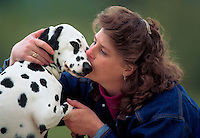 Woman kisses her dalmatian.
