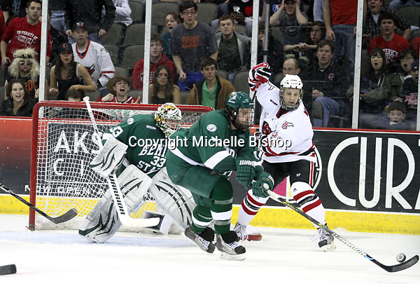 Bemidji State's Matt Carlson is able to get his stick on a loose puck as UNO's Matt White looks on during the third period. Bemidji State beat UNO 4-2 Friday night during the first round of the WCHA playoffs at Qwest Center Omaha. (Photo by Michelle Bishop)