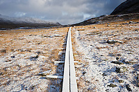 Wooden walkway through empty landscape with autumn snow, Kungsleden trail, Lapland, Sweden