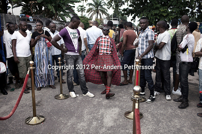 """KINSHASA, DEMOCRATIC REPUBLIC OF CONGO - FEBRUARY 10: Young Sapeurs parade and show their designer label clothes while paying their respect to Stervos Nyarcos, the founder of the .kitendi religion., which means clothing in local language Lingala. Nyarcos was known as the leader of the Sape movement, at Gombe cemetery on February 10, 2012 in Kinshasa, DRC. The word Sapeur comes from SAPE, a French acronym for Société des Ambianceurs et Persons Élégants. or .Society of Revellers and Elegant People. and it also means, .to dress with elegance and style"""". Most of the young Sapeurs are unemployed, poor and live in harsh conditions in Kinshasa,  a city of about 10 million people. For many of them being a Sapeur means they can escape their daily struggles and dress like fashionable Europeans. Many hustle to build up their expensive collections. Most Sapeurs could never afford to visit Paris, and usually relatives send or bring clothes back to Kinshasa. (Photo by Per-Anders Pettersson)"""