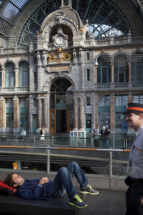 A tourist rests by a platform at Antwerp Central train station.