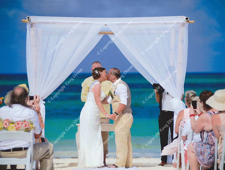 "Officiant Barry Strand says, ""You may kiss the bride."""