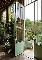 A view of the garden through the elegant metal door of the orangery