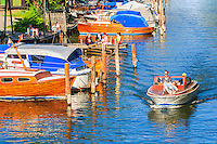Liten motorbåt med tre peroner far i Pålsundet Södermalm Stockholm där folk sitter på bryggor och njuter.