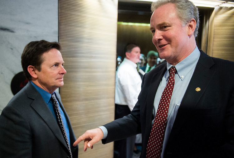 UNITED STATES - FEBRUARY 28: Sen. Chris Van Hollen, D-Md., right, chats with actor Michael J. Fox in the Hart Senate Office Building after their paths crossed at the elevators on Tuesday, Feb. 28, 2017. Fox was on Capitol Hill raising awareness for Parkinson's disease. (Photo By Bill Clark/CQ Roll Call)