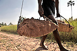 A man carries earth he has excavated in Khnach, a village in the Kampot region of Cambodia.