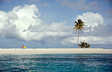 INDONESIA, Mentawai Islands, Kandui Resort, lone surfer walking on a small island with his surfboard