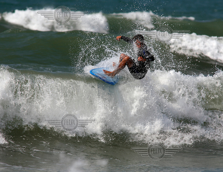 A surfer performs a floater, a maneuver in which the surfer rides over and/or along the top of a breaking wave. Bidart beach, near Biarritz,France.