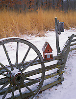 Bureau County, IL <br /> Red bird house perched on a snowy split rail fence with golden prairie grasses and oak forest in the background