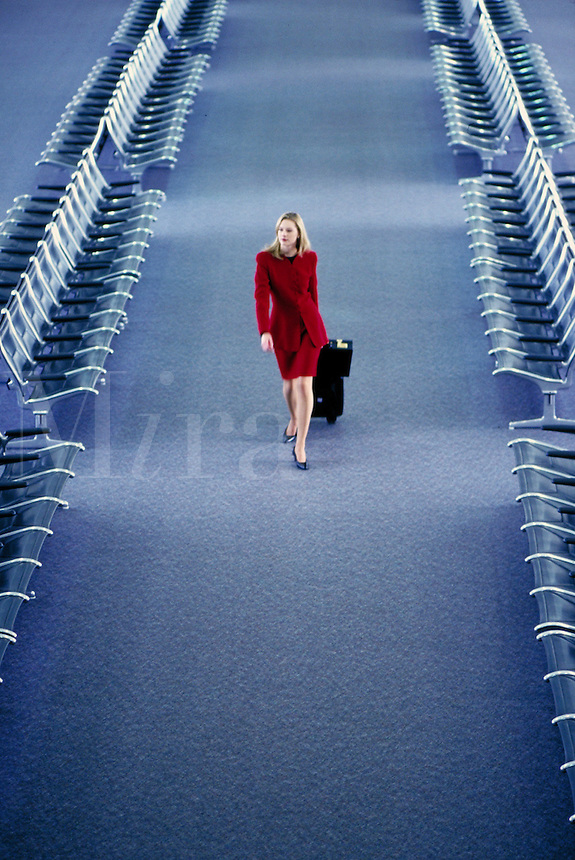 Businesswoman in a red business suit with a suitcase on wheels walking between rows of empty chairs at an airport. travel. L. Pigeon M.R.#L-13.