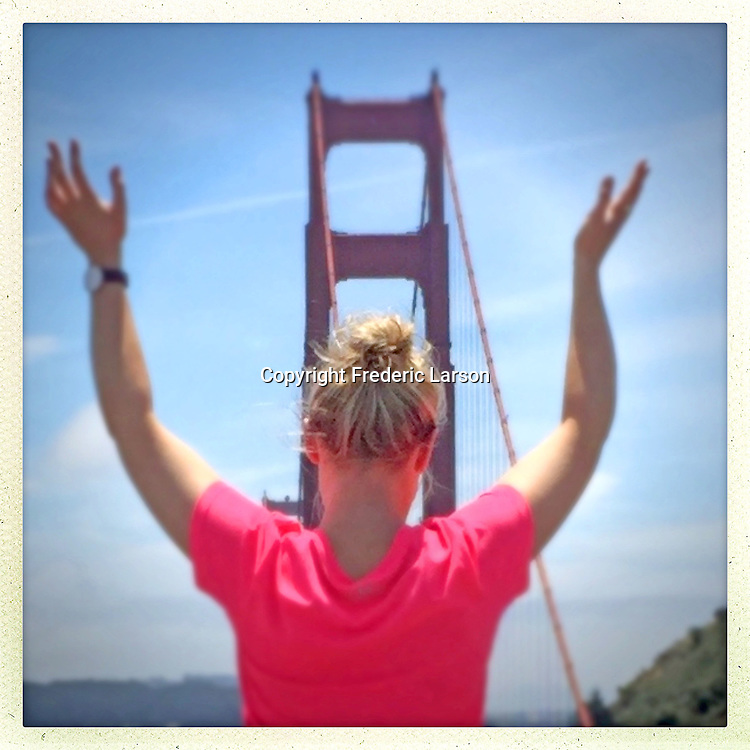 A woman at Vista Point Golden Gate Bridge  turnout rises her arms.