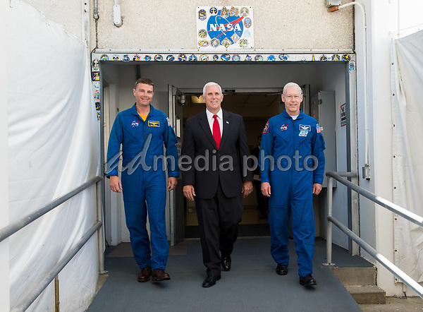 In this photo released by the National Aeronautics and Space Administration (NASA) United States Vice President Mike Pence, center, and NASA astronaut Reid Wiseman, left, and NASA astronaut Pat Forrester, right, walk out of the historic crew doors at Kennedy Space Center's (KSC) Operations and Checkout Building on Thursday, July 6, 2017, in Cape Canaveral, Florida. These are the same doors that Apollo and space shuttle astronauts walked through on their way to the launch pad. Photo Credit: Aubrey Gemignani/NASA/CNP/AdMedia