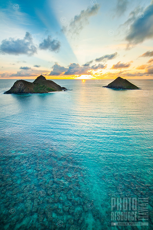 An aerial view of the sunrise and the Mokulua Islets or Islands off the shore of Lanikai, Windward O'ahu.
