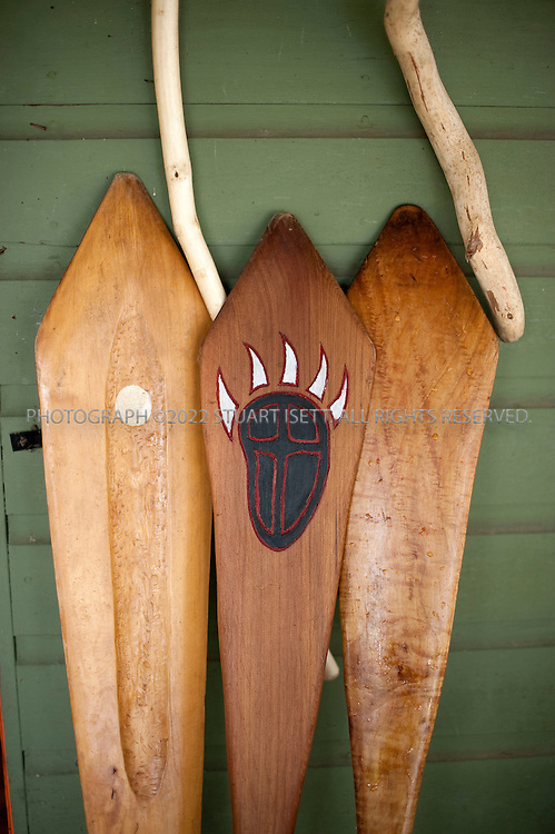5/7/2009--Sammamish, WA, USA..Paddles carved by John Mullen's students lean on the side of his cabin on Beaver Lake. John  is employed as the Snoqualmie tribe's master carver. Every year two dozen or so Snoqualmie Indians convene at the base of Snoqualmie Falls--a sacred tribal site-- to begin their annual Canoe Journey. This year a 100-mile voyage out into and across Puget Sound to a five-day powwow hosted by the Suquamish tribe at their reservation on the Kitsap Peninsula. Each year a different coastal or river-based Northwest tribe hosts the powwow, with dozens of other tribes paddling there celebrate their common culture and heritage. ..The Canoe Journey tradition has been instrumental in reviving an age-old Snoqualmie tribe tradition: wood carving. Needing canoes and paddles to accommodate all tribal members who want to go on the annual Canoe Journey, the tribe established a woodworking budget and secured a carving shed soon after it was re-acknowledged in 1999. These days, four tribal members, led by John Mullen (the brother of drum bearer Ray), work full-time at the shed, making dugout canoes out of old-growth red cedar trees and paddles out of big leaf maple wood, just like their forebears in centuries past. ...©2009 Stuart Isett. All rights reserved.