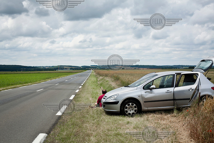Bene Michalowski waits by his car to see the Tour de France cycling competition pass by.