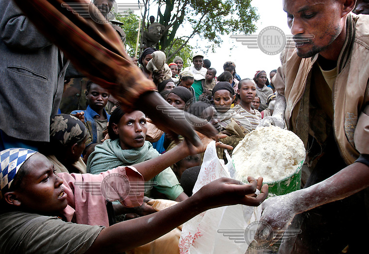 © Sven Torfinn / Panos Pictures..Ethiopia, Shebedino, May 2003.People waiting for food distribution..Employee of a local NGO is distributing relief food with a bucket among the population..Hunger, malnutrition, malnourished people, famine, drought, failed harvests, agricultural policies, rural population...Honger, hongersnood, ondervoeding, droogte, mislukte oogsten, landbouwbeleid, bevolking,