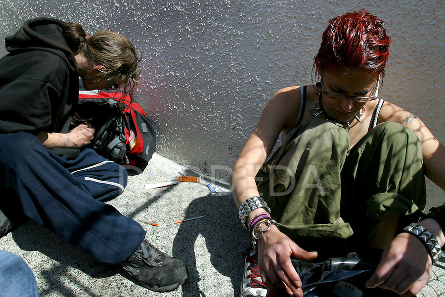 Two drug addicts pack up their belongings after the man in this image injected a needle into this young woman's jugular vein in her neck, in Victoria, BC, British Columbia, Canada. This area between two buildings is a common site for intravenous drug users to utilize as a shooting gallery. Photo shot for the GLOBE and MAIL.