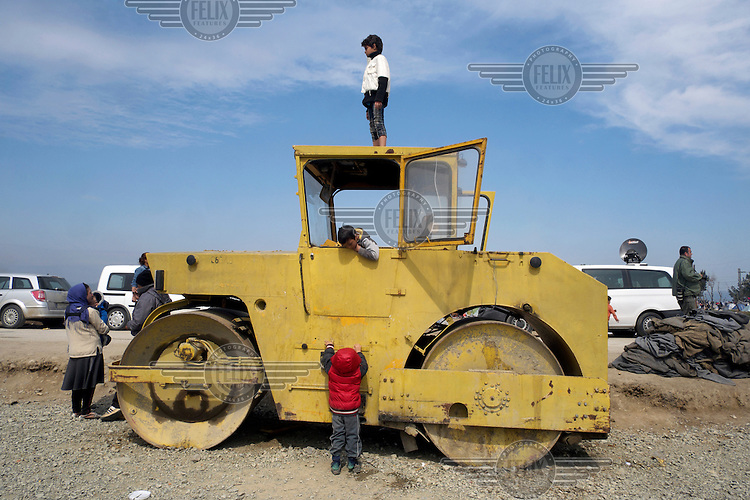 Children play on a disused road roller in the makeshift refugee camp at Idomeni. Around 14,000 people were stranded in the camp which the authorities have since closed and distributed the occupants among several official camps around the country.