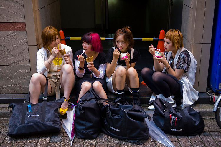 Teenage girls eat ice-cream from Baskin-Robbins on a sidewalk in the Shibuya District, Tokyo, Japan.