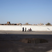 A man on a motorcycle waits for a group of women in Islamic Cairo. View from the ancient walls. Egypt, 2012.
