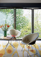 A pair of leather chairs by Harry Bertoia on an abstract rug in a corner of the living room