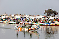 Senegal, Saint Louis.  Fishermen Head to Sea while  Refrigerated Trucks Line up to Buy and Carry Fishermen's Catch to Inland Markets.  Fishermen's Cemetery on Ridge in Background.